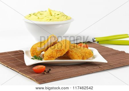 bowl of mashed potato puree with chopped chives and plate of breaded turkey breast on brown place mat - close up