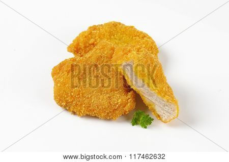 breaded turkey breasts on white background
