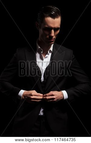 portrait of elegant man in black tuxedo posing in dark studio background while looking away and closing his jacket