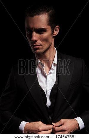 portrait of young businessman in black suit posing in dark studio background closing his jacket and looking away