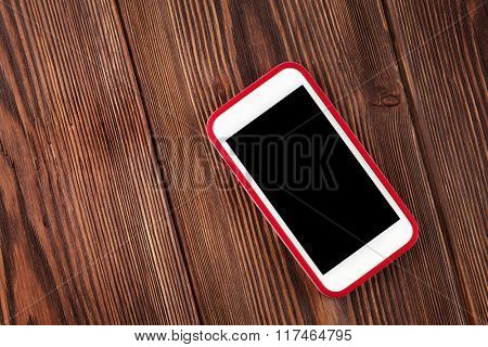 Smartphone on wooden table. Top view with copy space
