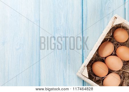 Eggs in wooden box over wood background. Top view with copy space