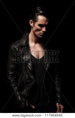 dark portrait of handsome rocker posing in studio background while looking away with hand in pocket