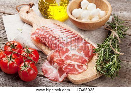 Prosciutto and mozzarella on wooden table