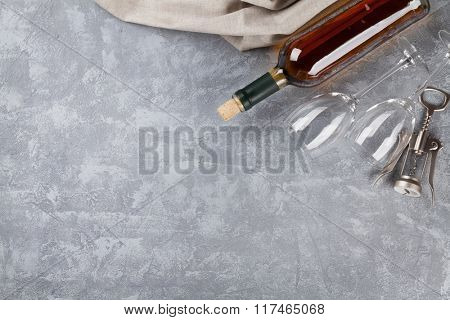 White wine bottle, glasses and corkscrew over stone background. Top view with copy space