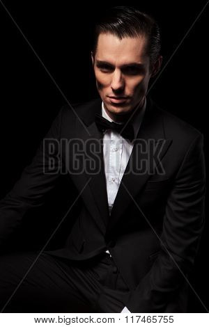 portrait of confident handsome model in black suit posing seated while looking at the camera in dark studio background