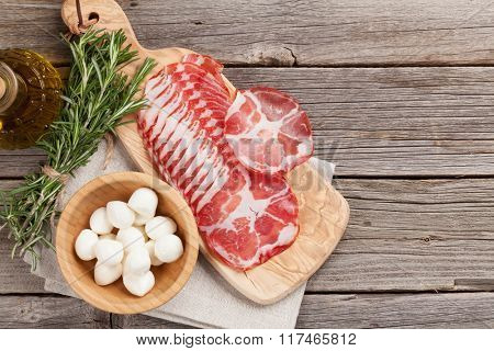 Prosciutto and mozzarella on wooden table. Top view with copy space