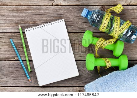 Diet and fitness concept. Dumbbells, water, tape measure and notepad for copy space
