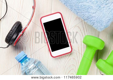 Fitness and diet concept. Dumbbells, water bottle, smartphone, headphones and towel. Top view with copy space