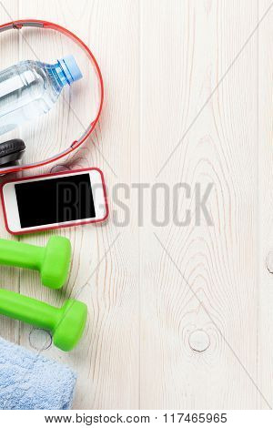 Fitness and diet concept background. Dumbbells, water bottle, smartphone, headphones and towel. Top view with copy space
