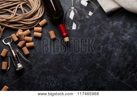 Red wine bottle, glasses and corkscrew over dark stone background. Top view with copy space