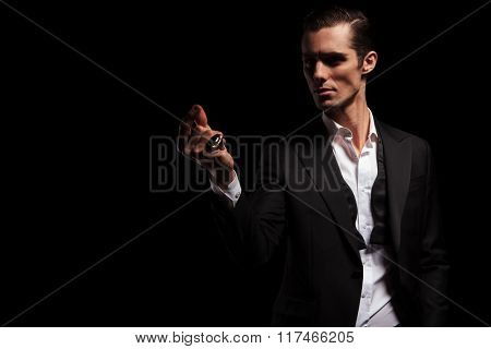 portrait of elegant man in black jacket posing in dark studio background looking away while snapping fingers