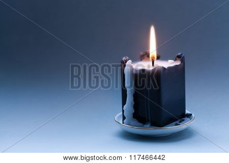 Black candle with a flame and drips. Dark blue gradient background. Greeting holiday card template.