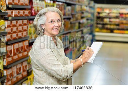 Senior woman checking list at the supermarket looking back at the camera