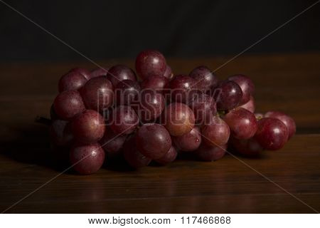 A bunch of red grapes over wooden background