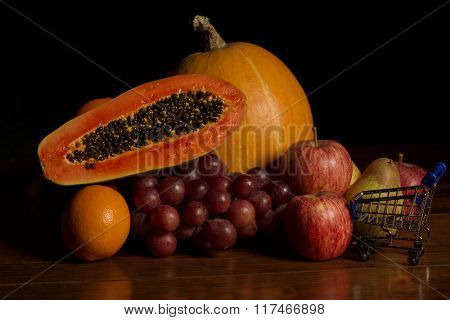 variety of fruits and a small shopping cart on a wooden table, studio picture