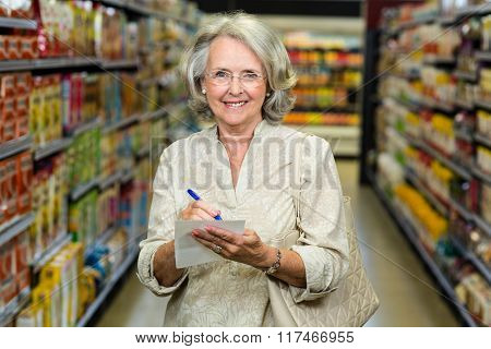 Smiling senior woman checking list and looking at the camera