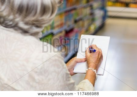 Rear view of senior woman checking list at the supermarket