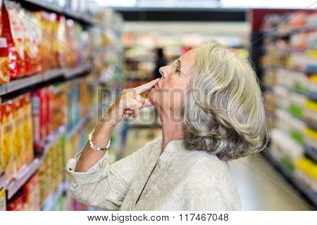Senior woman choosing food with finger on mouth