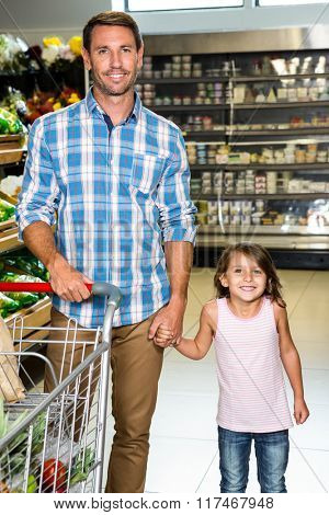 Smiling father and daughter in grocery store