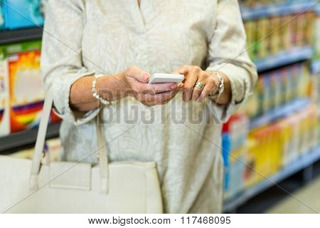 Mid section of woman using smartphone at the supermarket