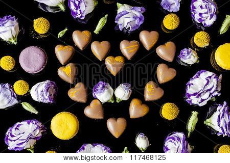 Milk chocolates heart surrounded with flowers from above on black