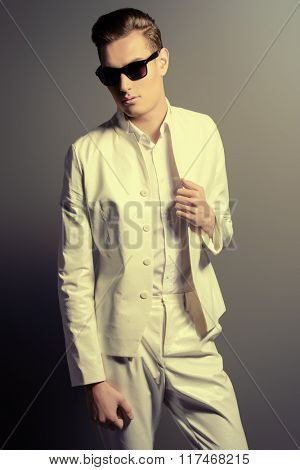 Elegant young man in white suit and sunglasses. Studio fashion shot.