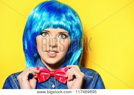 Modern girl wearing bright blue wig and jeans clothes posing over yellow background. Beauty, fashion.