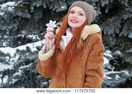 Girl portrait at winter outdoor, showing big snowflake toy.