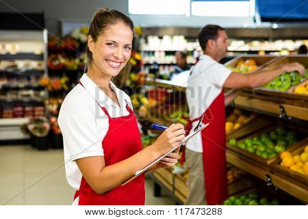 Grocery store staff with clipboard in grocery store