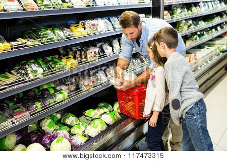 Happy family shopping vegetables at the grocery store