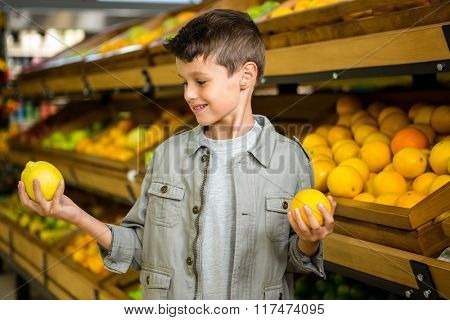 Little boy holding lemons in grocery story