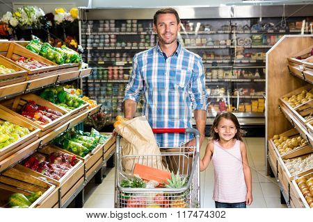 Portrait of father and daughter in grocery store