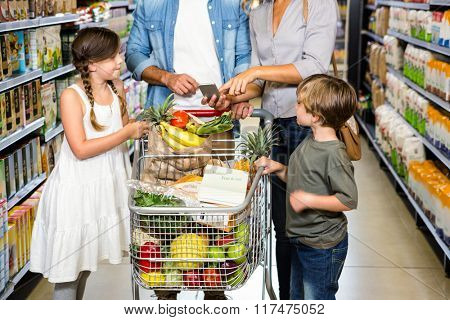 Cute family doing grocery shopping together at the supermarket