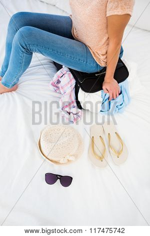 Woman sitting on her overfull suitcase at home