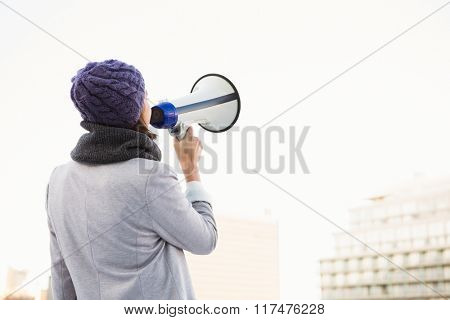 Rear view of woman shouting with megaphone outdoor