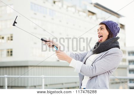 Happy woman using selfie stick outside