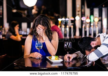 Couple laughing and having a drink in a bar