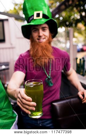 Disguised man holding a green pint for St Patricks day