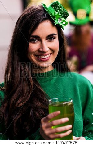 Portrait of woman celebrating St Patricks day with a green pint