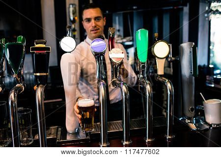 Barman serving a pint of beer in a bar