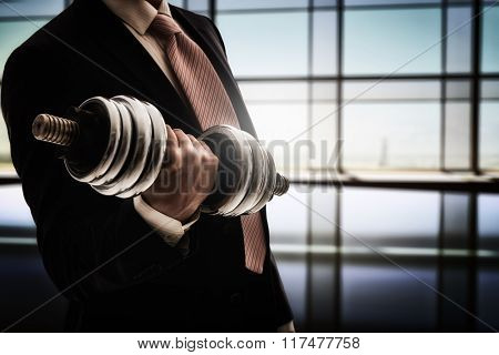 successful business man holding a heavy dumbbell. the concept of success in a hard work of business.