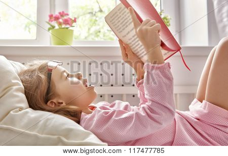 cute child girl reading a book. self learning