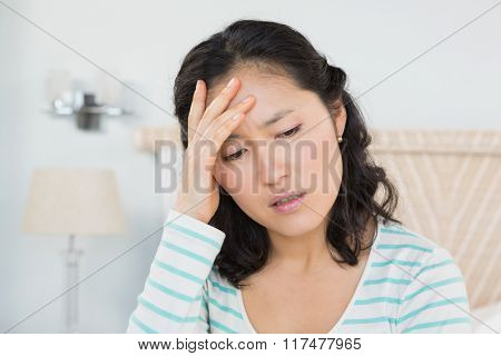 Woman with head ache sitting on bed at home