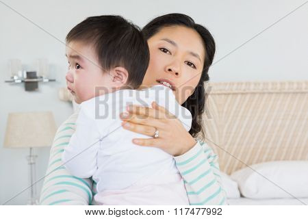 Lovely mother holding baby daughter on the bed
