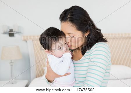 Lovely mother carrying baby daughter in bedroom