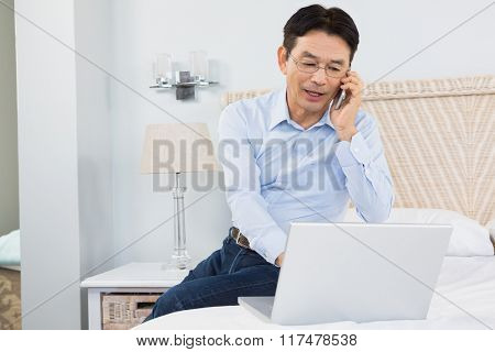 Man on a phone call using laptop in bedroom