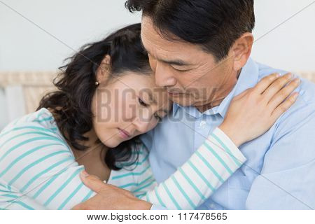 Sad couple embracing at home