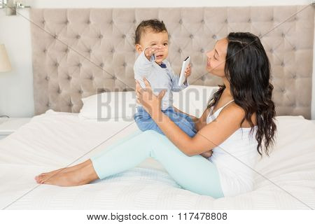 Happy brunette holding her baby who is holding smartphone on bed