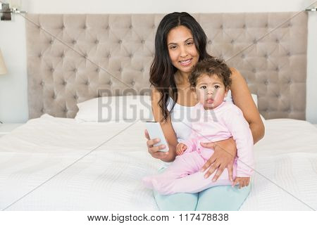Smiling brunette holding her baby and using smartphone on the bed